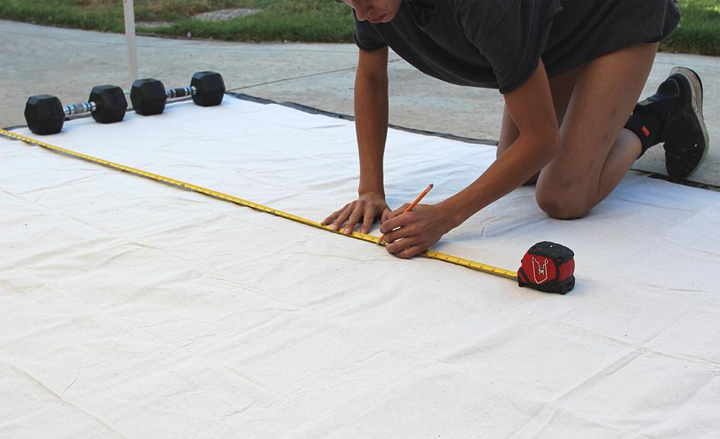 Một người đo chiều dài của màn chiếu tự làm.