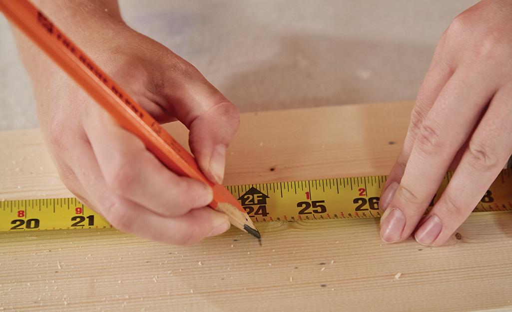 Người đo một mảnh gỗ và làm dấu.
