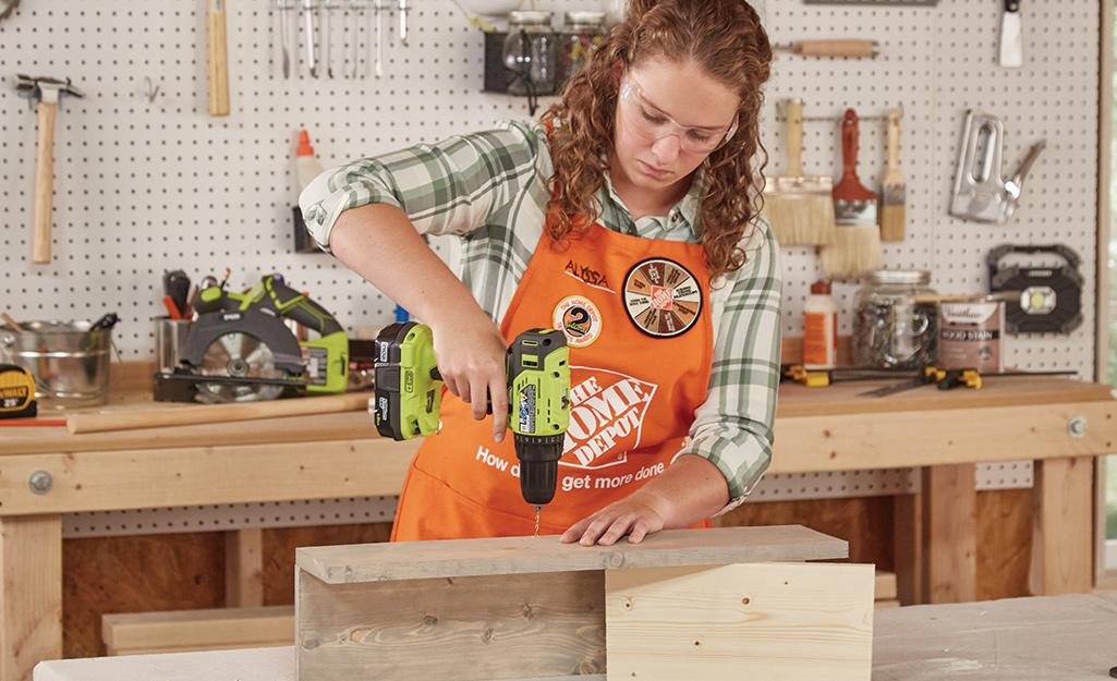 Người phụ nữ đang khoan vào một mảnh gỗ.