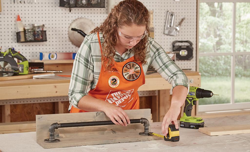 Người phụ nữ sử dụng thước đo để căn chỉnh các mảnh.