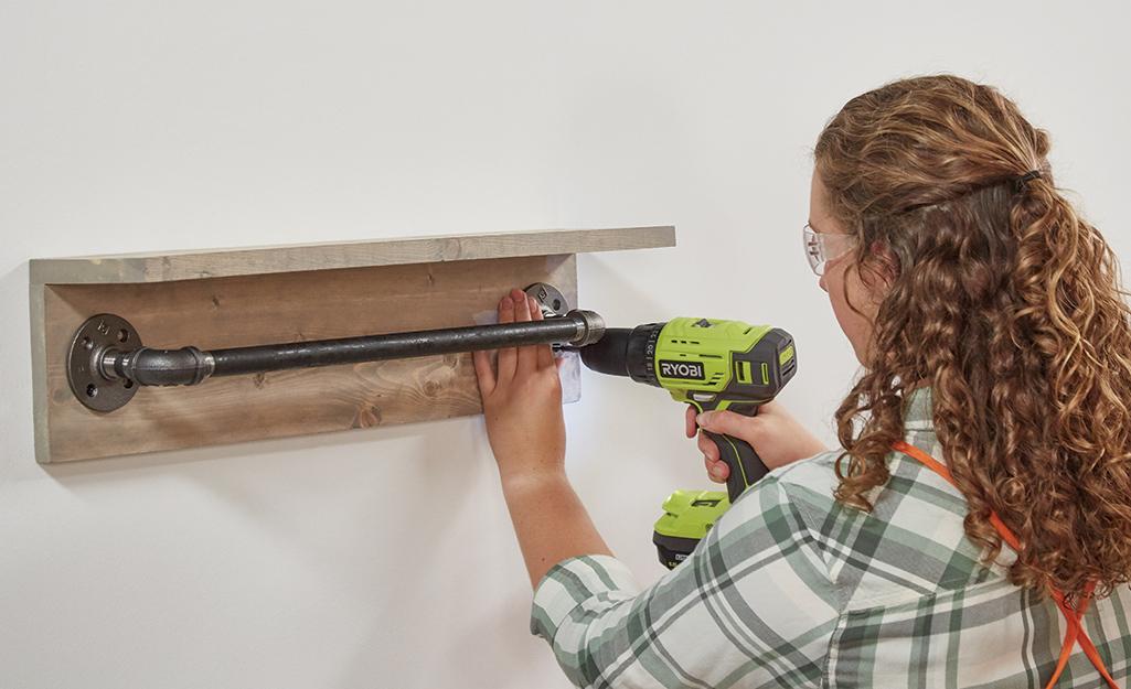 Người phụ nữ gắn thanh khăn ống vào tường.