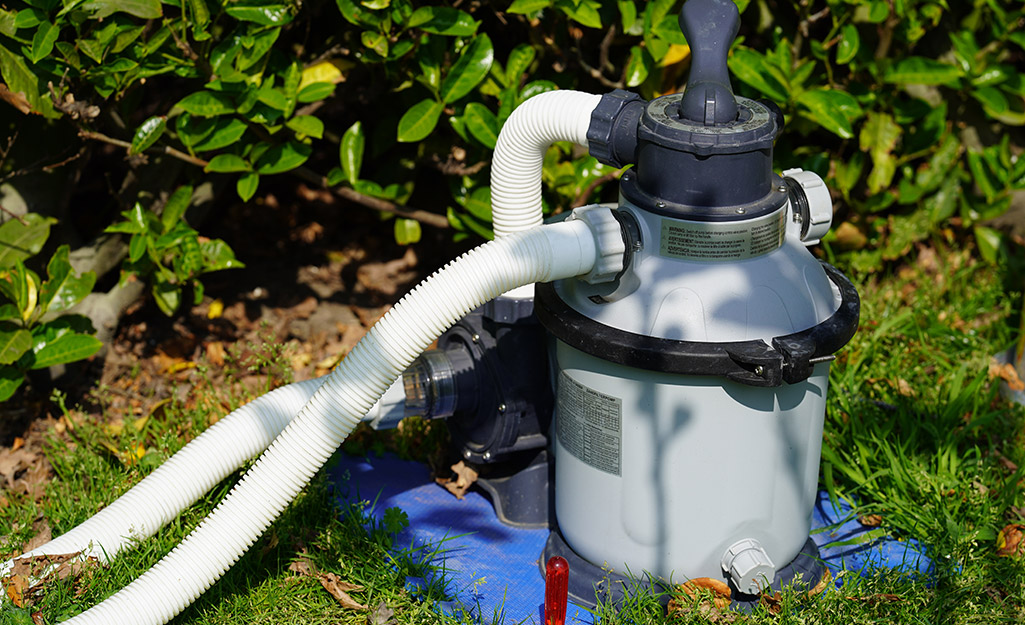 A pool pump sitting on the grass.