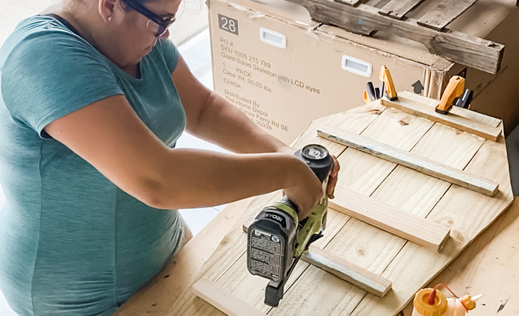 A woman uses a nail gun to secure braces to fence pickets.