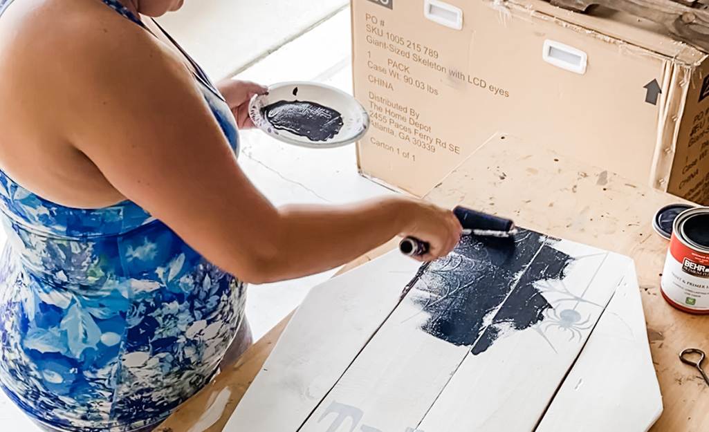 A woman uses a paint brush to apply black paint to fence pickets.