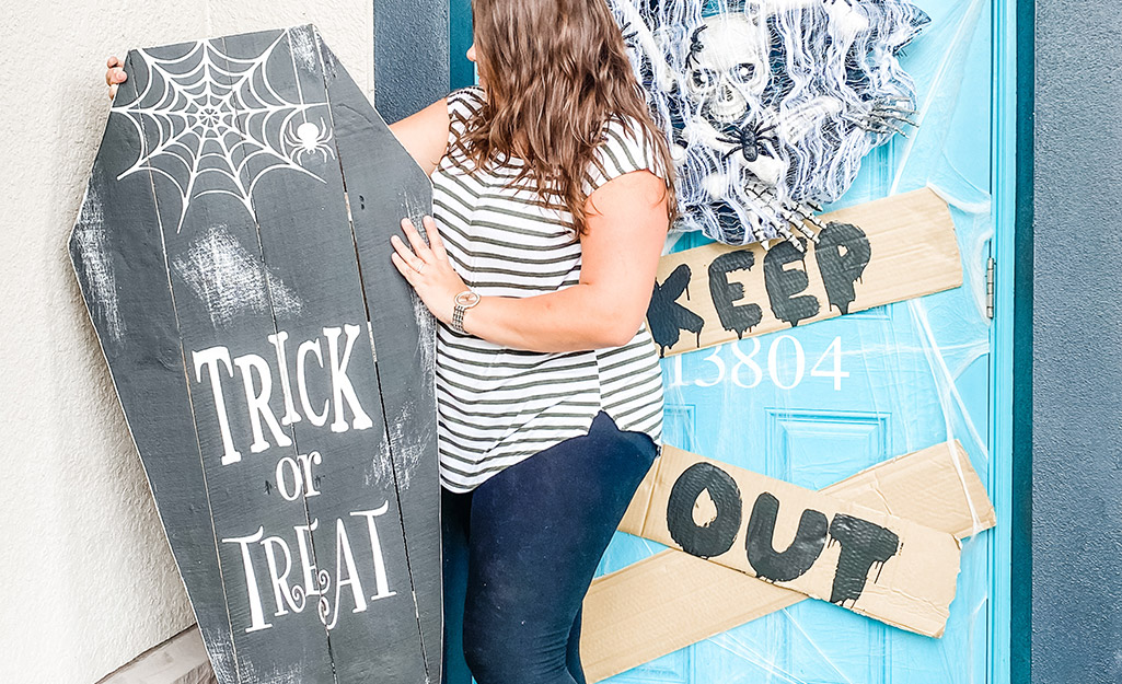 A woman decorates a front porch with her DIY sign.