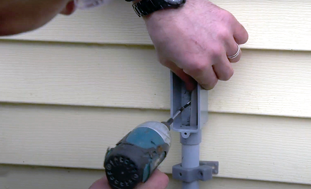 A person secures the conduit to a wall.