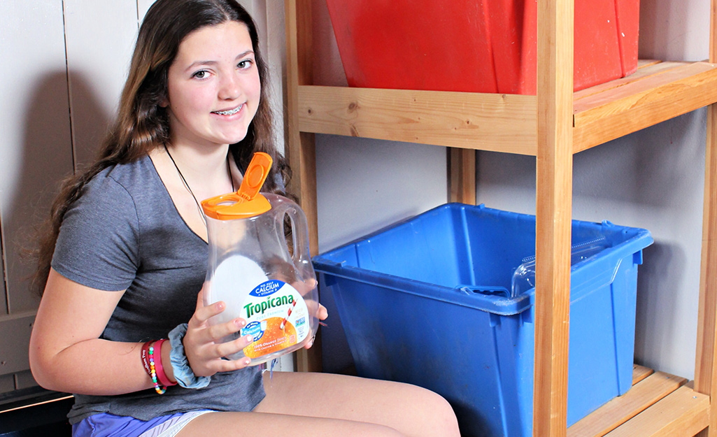 A girl holding an empty container in a storage space.