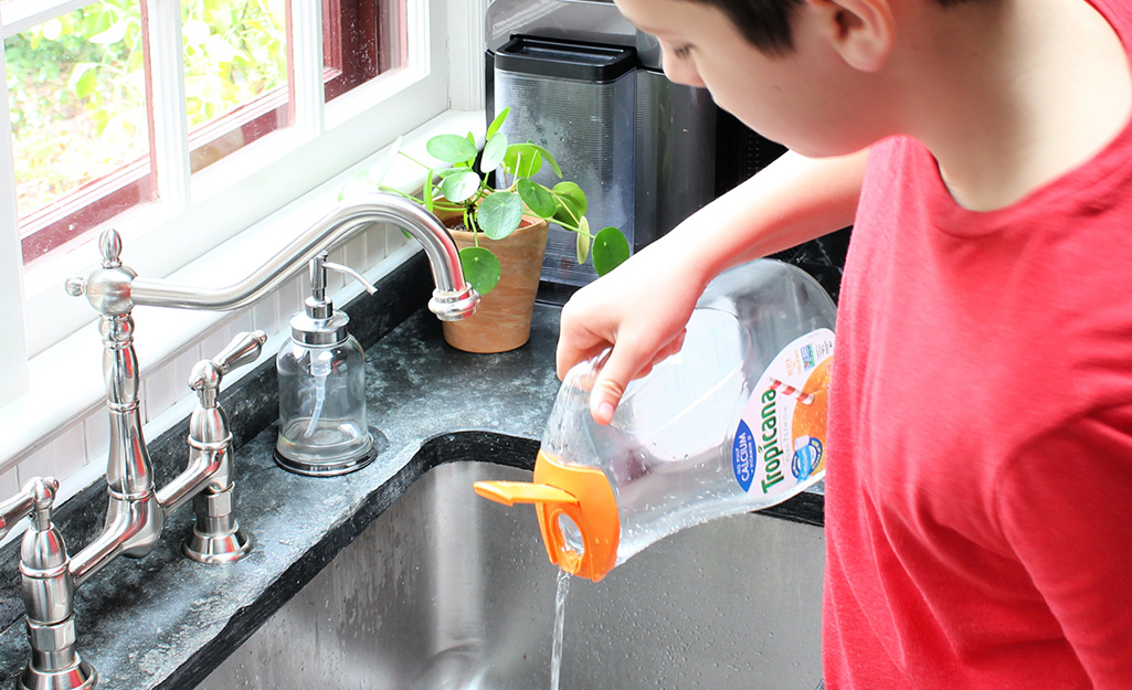 A boy pouring liquid out of a juice container.