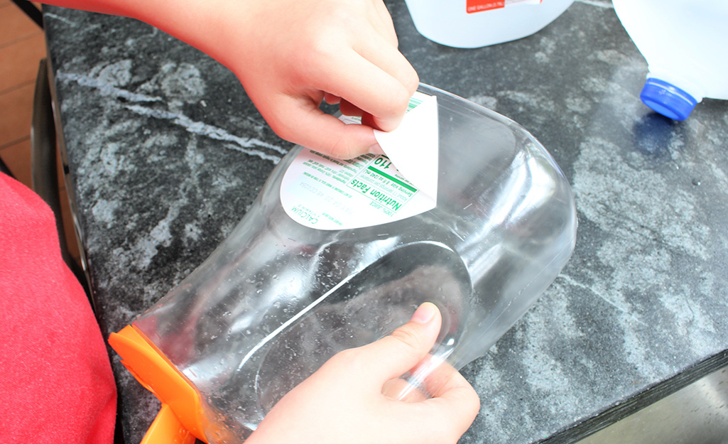 A hand removing a label from an empty container.