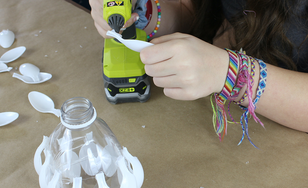 A girl applying hot glue to a plastic spoon.