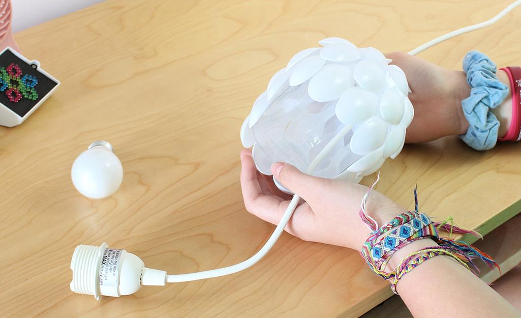 A power cord being threaded through a DIY lamp.