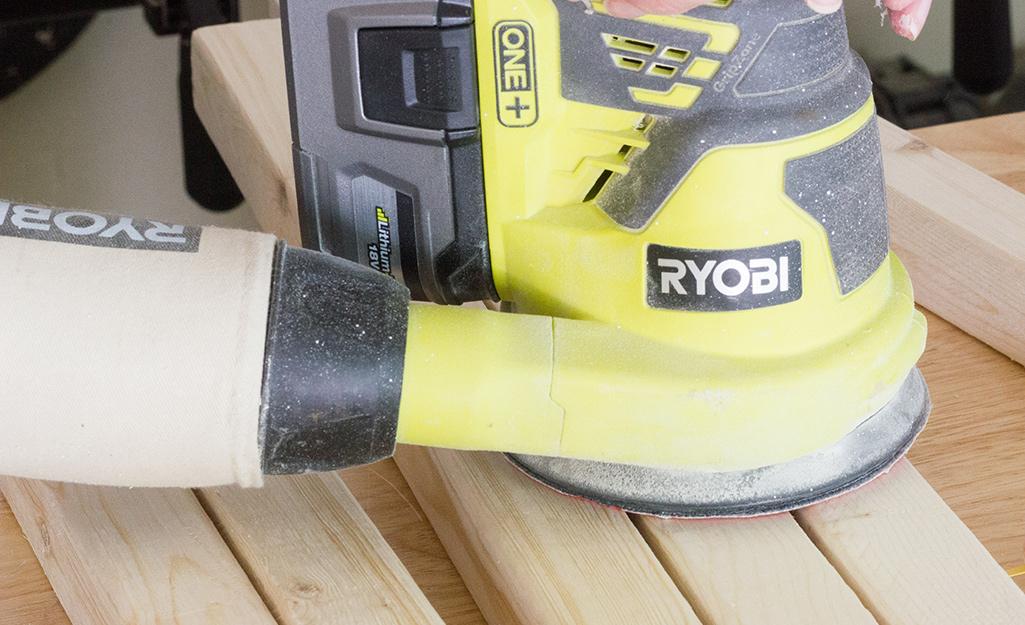 Sander sanding a piece of wood.