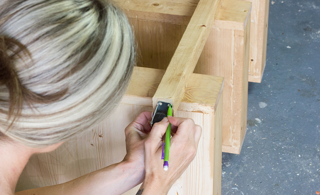 Person marking to add casters to the wood cart.
