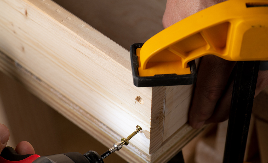 A drill securing screws into plywood.