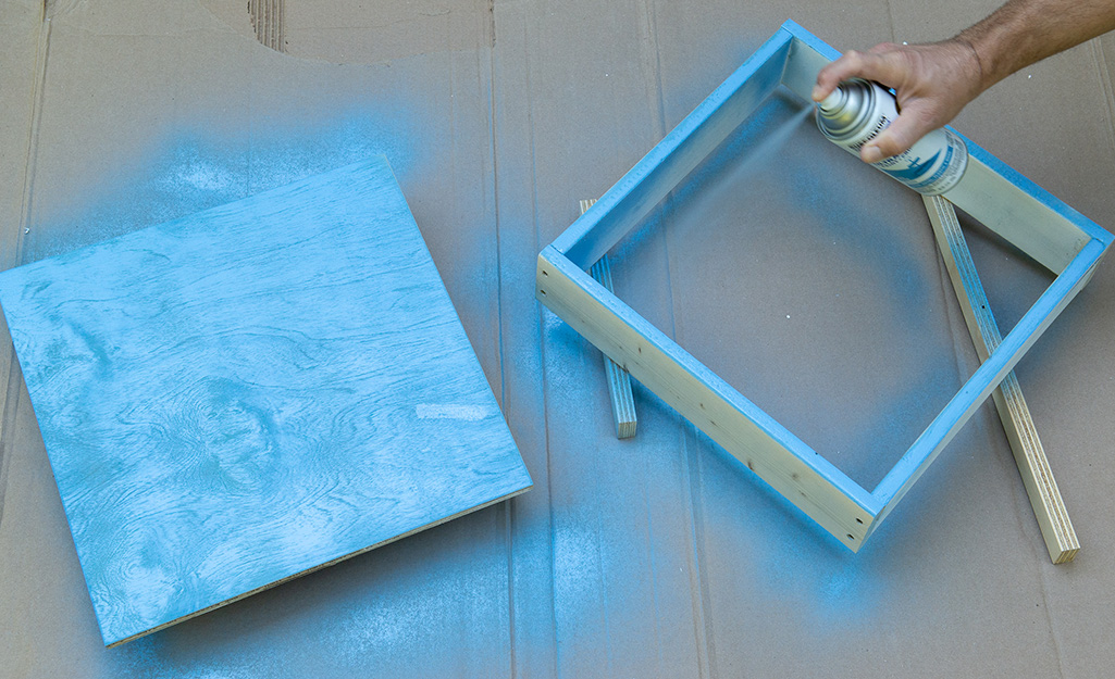 A person spraying blue paint onto plywood pieces.
