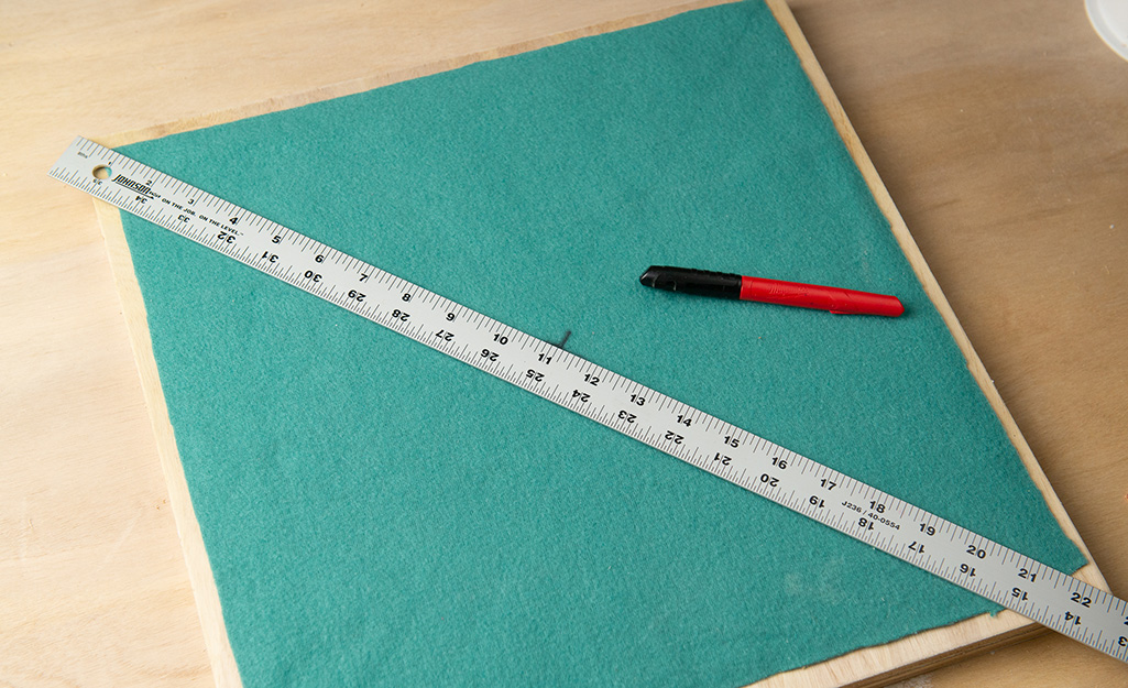 A ruler laying across a square of plywood covered in felt.