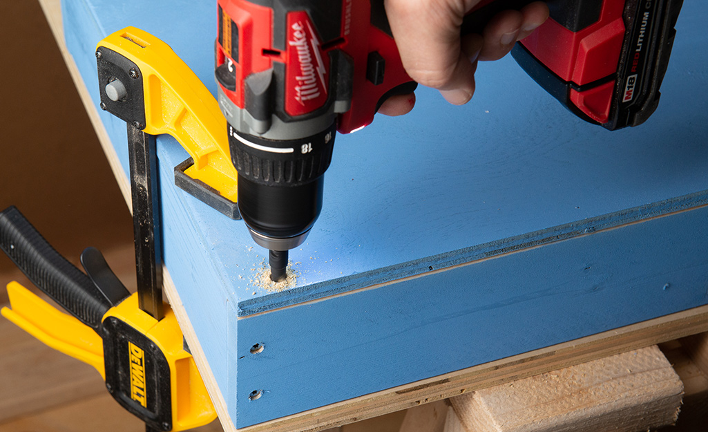 A drill securing pieces of plywood.