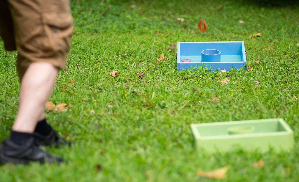 A man in a backyard playing with a DIY washer toss set.