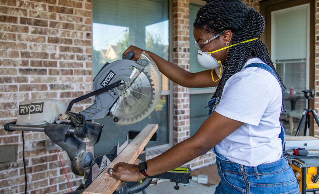 Một người phụ nữ dùng cưa để cắt một khúc gỗ.