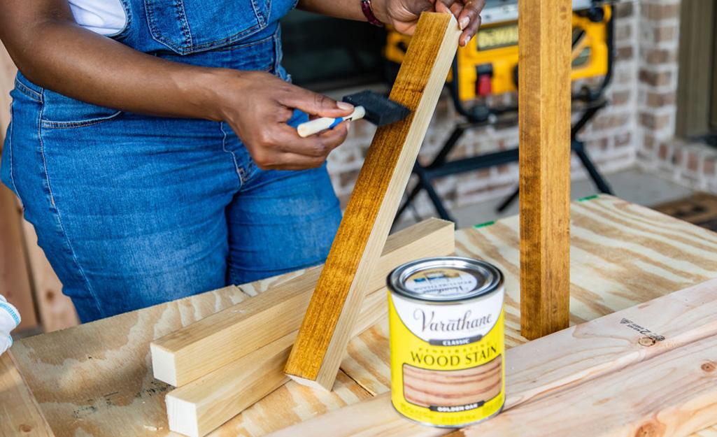 Một người phụ nữ đang nhuộm hai mảnh gỗ.