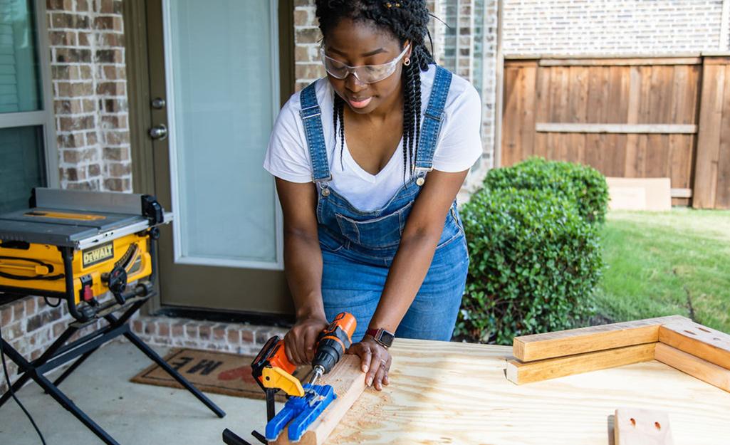 Một người phụ nữ sử dụng máy khoan trên một mảnh gỗ.