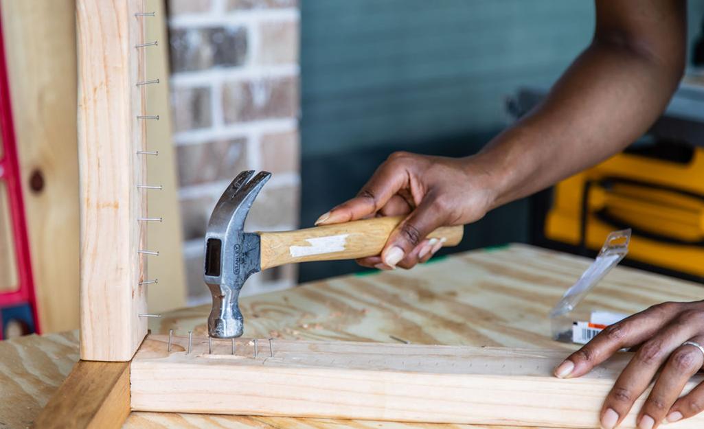 Cận cảnh bàn tay đóng đinh vào khung băng ghế gỗ.