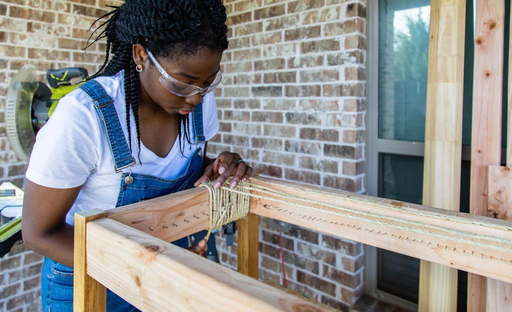 Một người phụ nữ đang buộc dây thừng quanh khung của một chiếc ghế dài.