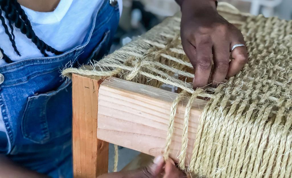 Hai tay đan sợi xe dọc theo đầu băng ghế.