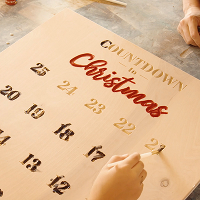A person paints in the numbers on a Christmas countdown calendar.