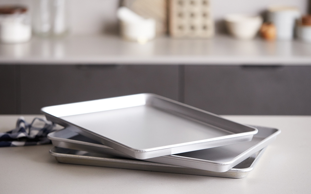 A collection of rimmed baking sheets on a counter.