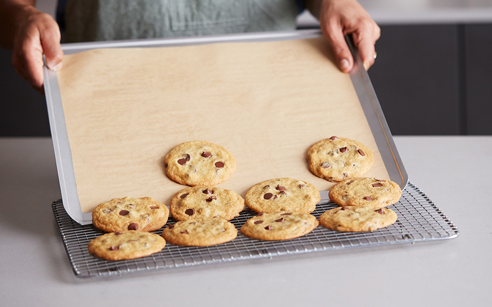 A person sliding cookies off of a rimless baking sheet.