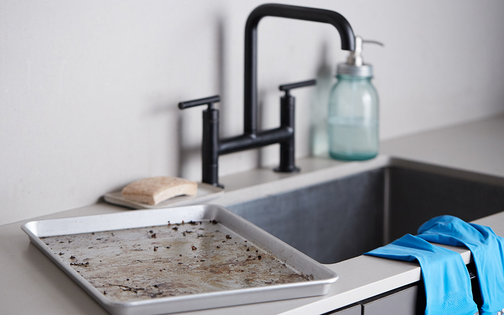 A baking sheet beside a kitchen sink.