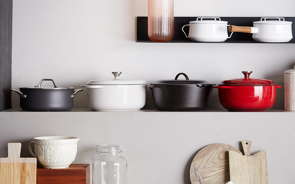An assortment of Dutch ovens on a kitchen shelf.