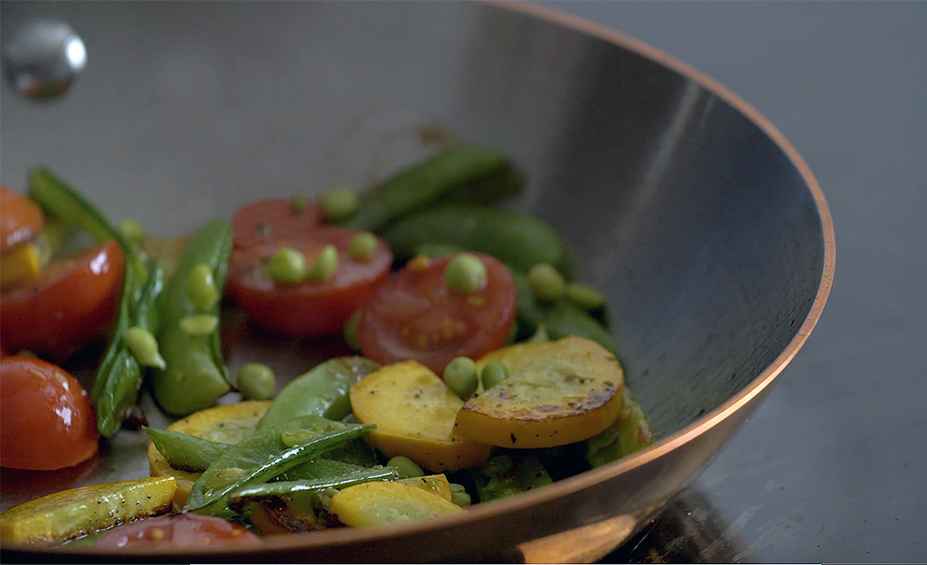 Vegetables are sauteed in a copper frying pan.