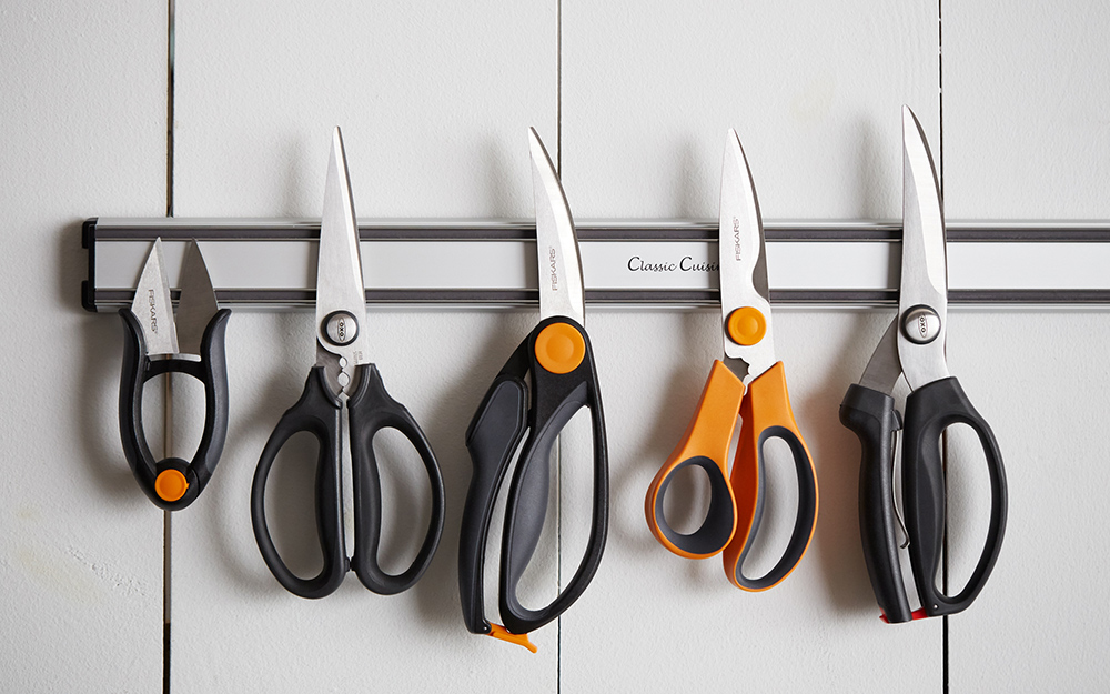 An assortment of kitchen shears on a magnetic strip.
