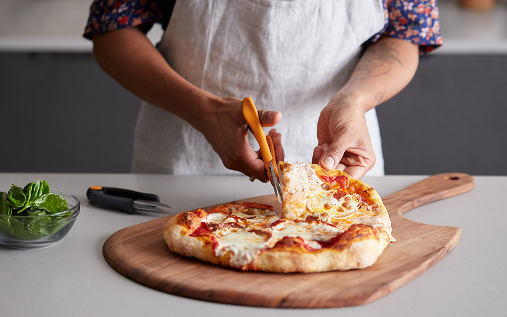 A person cutting pizza with pizza shears.