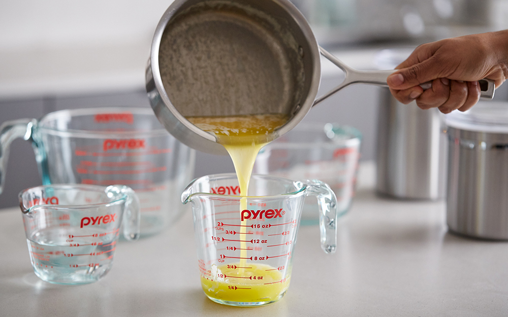 A person pouring melted butter into a liquid measuring cup.