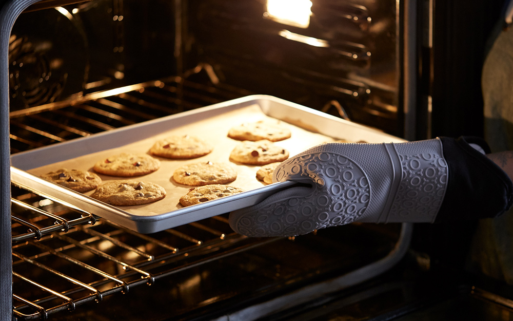 A person using a silicone oven mitt to pull a baking sheet.