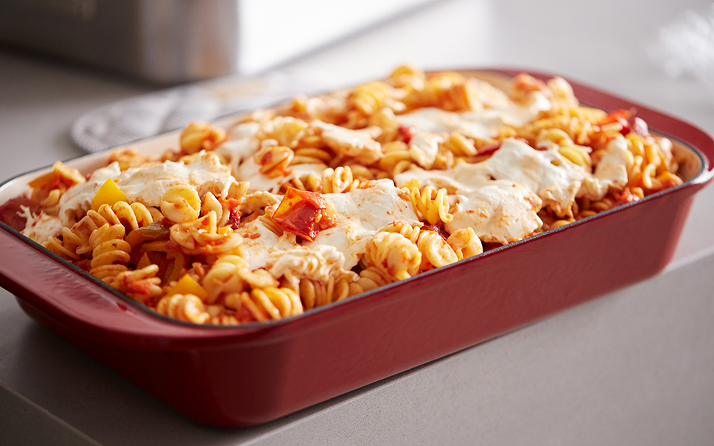 A red ceramic roasting pan with a baked pasta dish in it.