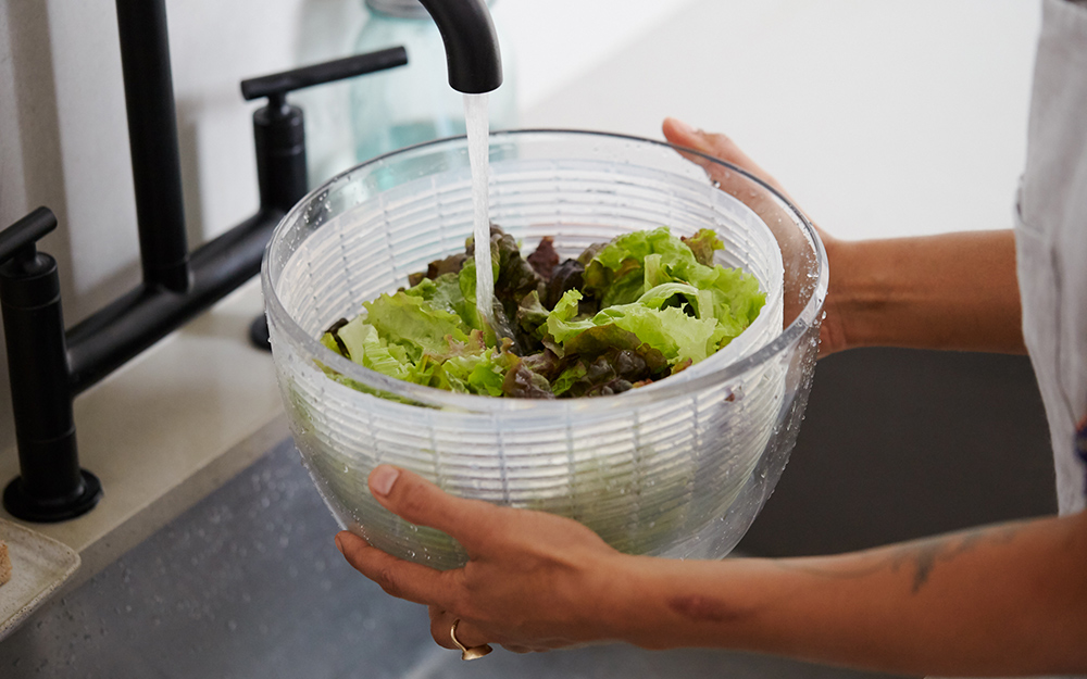 A person rinsing green in a salad spinner.