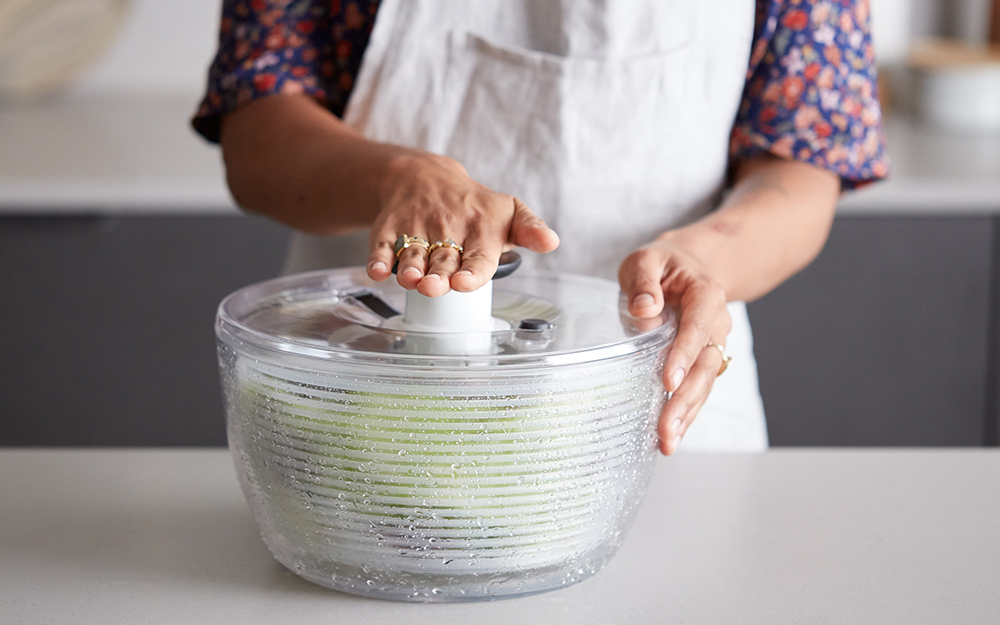 A person operating the pump on a salad spinner.