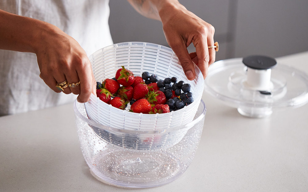 A person rinsing a salad spinner full of assorted berries.