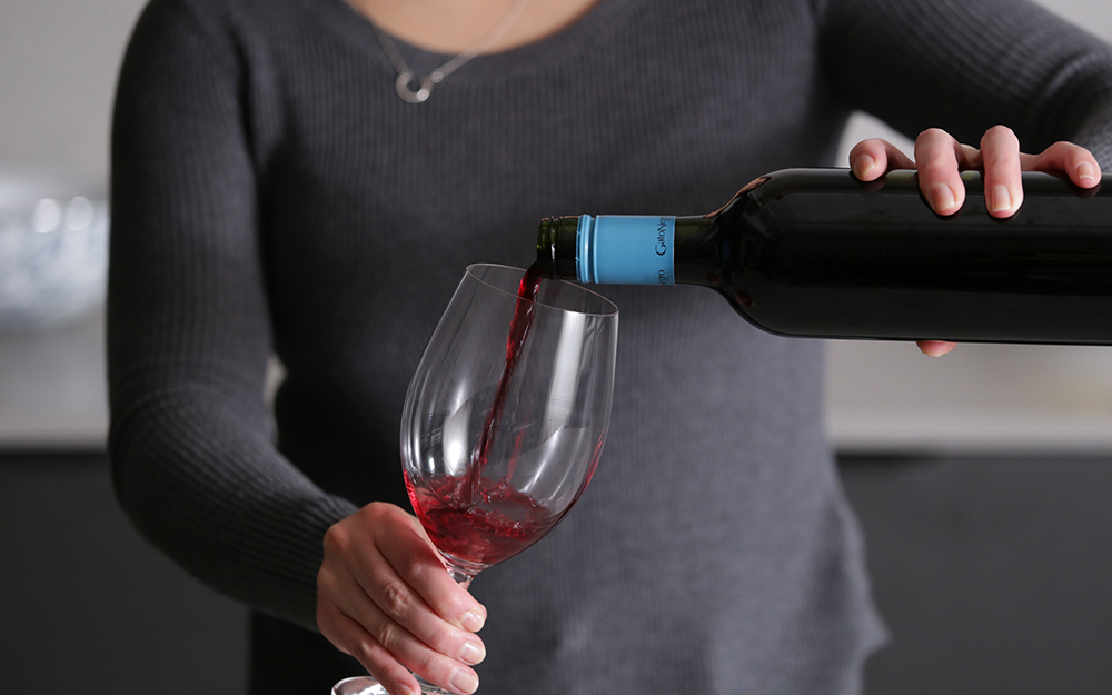 Một người rót vào ly rượu đỏ.