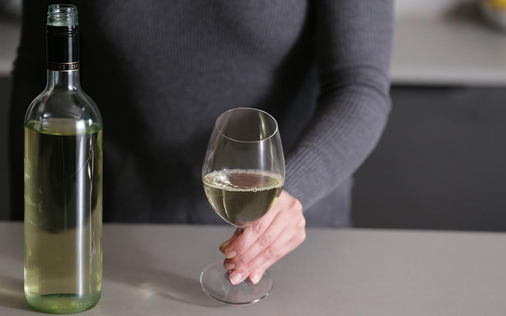 Một người với một ly rượu trắng và một chai rượu