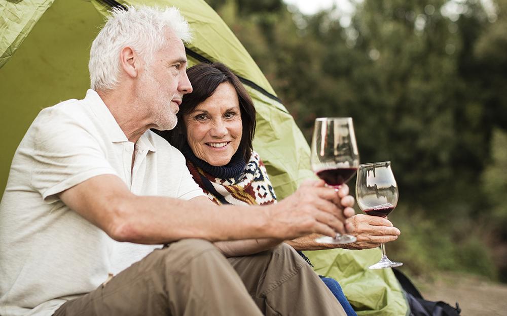 Một cặp vợ chồng ngồi cầm ly rượu bên cạnh một chiếc lều xanh.