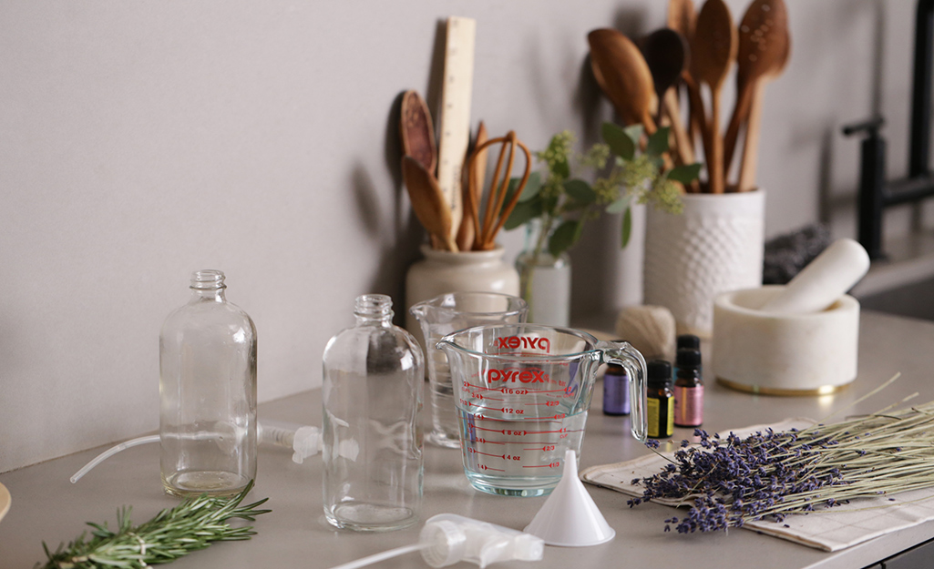 Dried herbs lying on counter with measuring cup and spray bottle