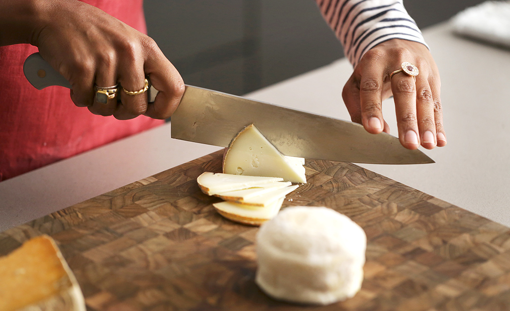 A woman slices cheese on a charcuterie board.