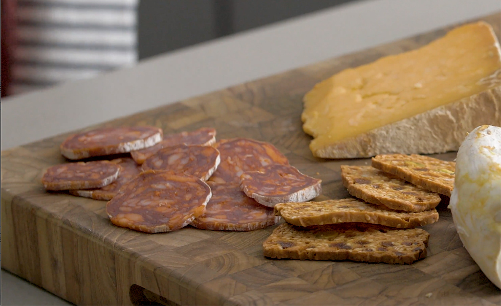 Pepperoni is displayed next to crackers and cheese on a board.