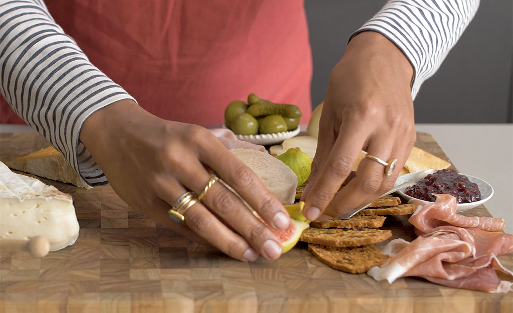 A woman adds fruit and olives to her board.