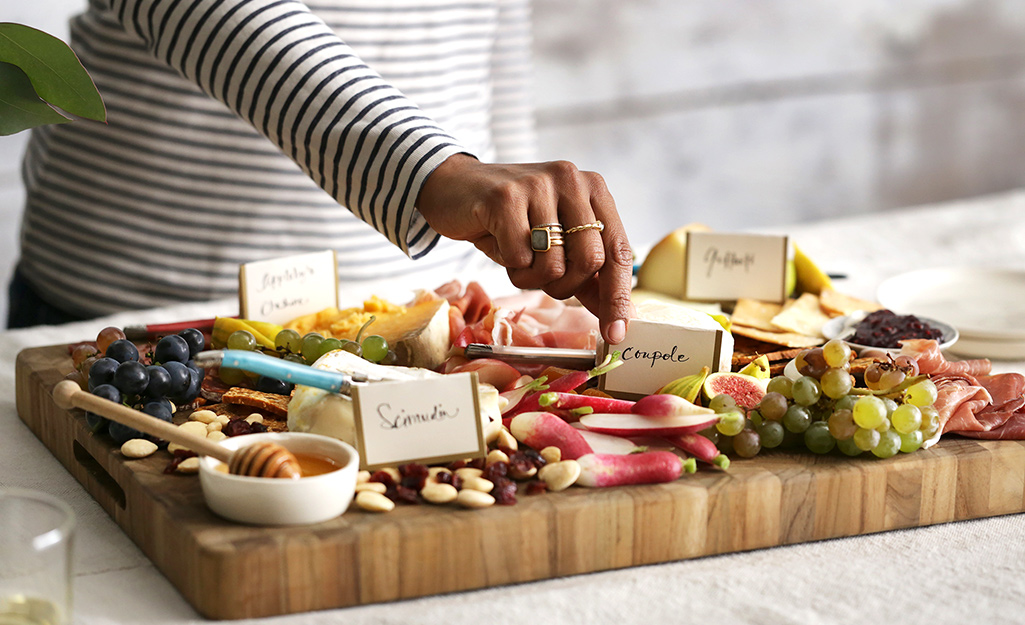 A woman labels the items on her charcuterie board for guests.